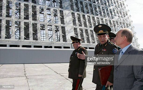 Russian President Vladimir Putin listens to Colonel General Vladimir Popovkin , commander-in-chief of the space forces, during his visit to a...