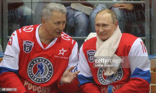 Russian President Vladimir Putin listens to former Soviet ice hochey player and coach Alexander Yakushev during the gala match of the Night Hockey...