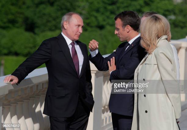 Russian President Vladimir Putin listens to French President Emmanuel Macron as French First Lady Brigitte Macron stands nearby during a welcoming...