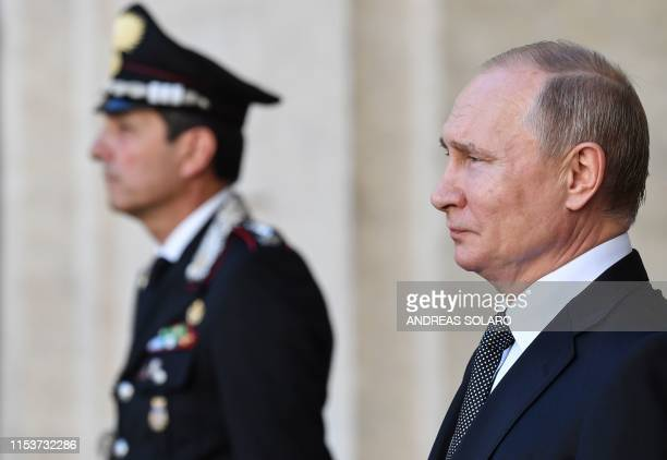Russian President Vladimir Putin listens to national anthems during a welcoming ceremony upon his arrival for a meeting with his Italian counterpart...