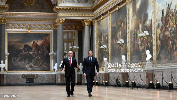 TOPSHOT Russian President Vladimir Putin looks around as he walks in the Galerie des Batailles as he arrives with French President Emmanuel Macron...