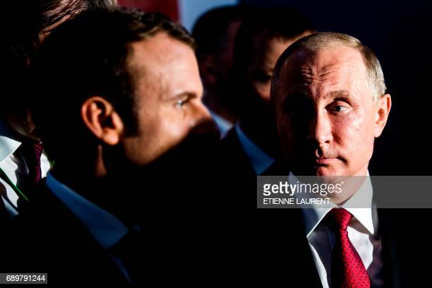 Russian President Vladimir Putin looks at French President Emmanuel Macron as they visit an exhibition about Russian emperor Peter the Great at the...