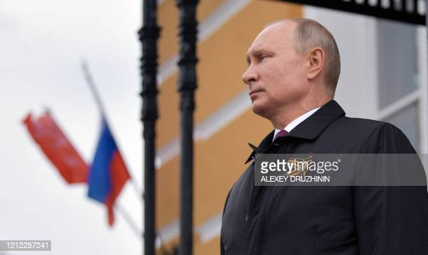 TOPSHOT Russian President Vladimir Putin looks at military aircrafts flying over the Kremlin and Red Square to mark the 75th anniversary of the...