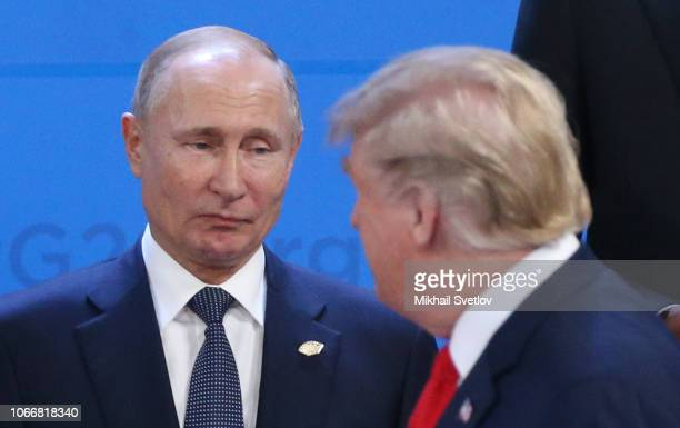 Russian President Vladimir Putin looks at U.S. President Donald Trump during the welcoming ceremony prior to the G20 Summit's Plenary Meeting on...
