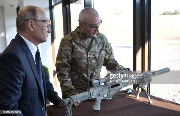 Russian President Vladimir Putin looks on as he tries out a Chukavin sniper rifle during a visit to the military Patriot Park in Kubinka outside...