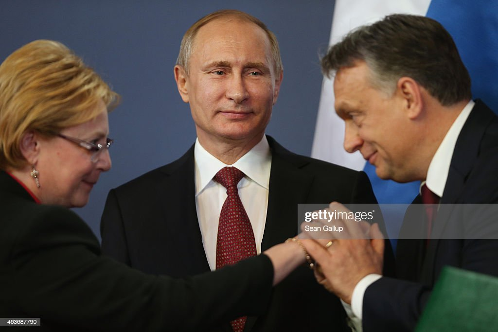Russian President Vladimir Putin (C) looks on as Hungarian Prime Minister Viktor Orban kisses the hand of a member of the Russian delegation during a signing ceremony of several agreements between the two countries on February 17, 2015 in Budapest, Hungary. Putin is in Budapest on a one-day visit, his first visit to an EU-member country since he attended ceremonies marking the 70th anniversary of the D-Day invasions in France in June, 2014.