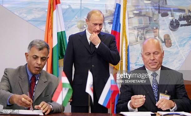 Russian President Vladimir Putin looks on as the head of Rosoboronexport, state arms trading company, Sergei Chemezov and Hindustan Aeronatics...