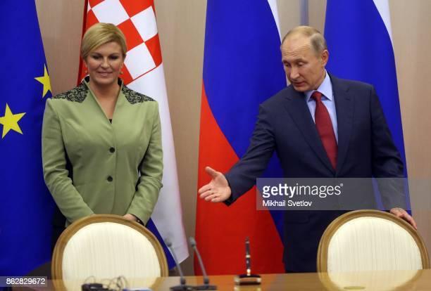 Russian President Vladimir Putin looks on Croatian President Kolinda GrabarKitarovic during their meeting on October 18 2017 in Sochi Russia...