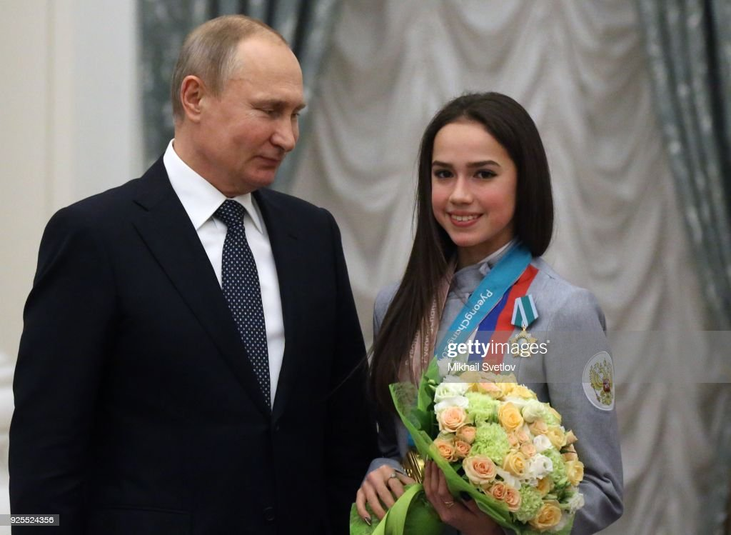 Russian President Vladimir Putin (R) looks on figure skater Alina Zagitova (R) during his meeting with athlets from Russia who took part in the 2018 Winter Olympic Games at the Kremlin on February 28, 2018 in Moscow, Russia.