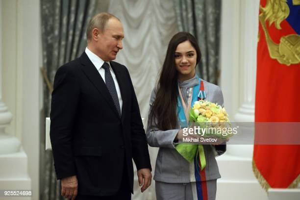 Russian President Vladimir Putin looks on figure skater Yevgenia Medvedeva during his meeting with athlets from Russia who took part in the 2018...