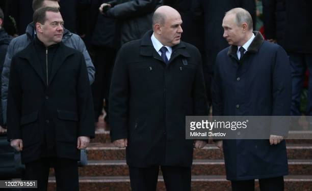 Russian President Vladimir Putin looks on Prime Minister Mikhail Mishustin and Deputy Chairman of the Security Council Dmitry Medvedev during the...