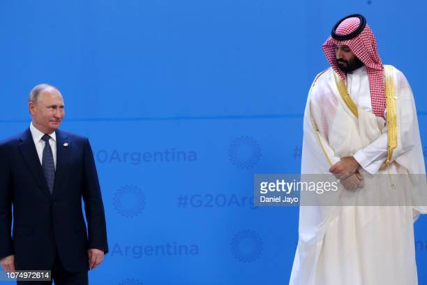 Russian President Vladimir Putin looks over at Crown Prince of Saudi Arabia Mohammad bin Salman al-Saud as they line up for the family photo during...