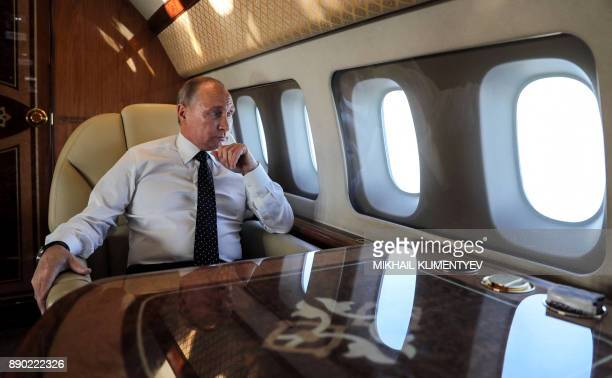 Russian President Vladimir Putin looks through the porthole while aboard the presidential plane during the approach to the Russian air base in...