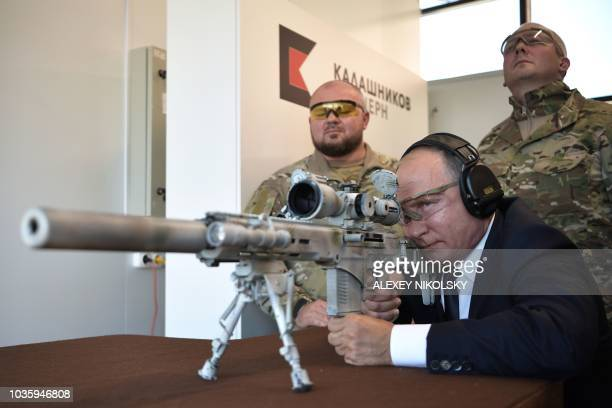 TOPSHOT Russian President Vladimir Putin looks through the scope as he shoots a Chukavin sniper rifle during a visit to the military Patriot Park in...