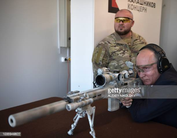 Russian President Vladimir Putin looks through the scope as he shoots a Chukavin sniper rifle during a visit to the military Patriot Park in Kubinka...