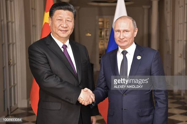 Russian President Vladimir Putin meets with his Chinese counterpart Xi Jinping on the sidelines of the 10th BRICS summit on July 26 2018 in...