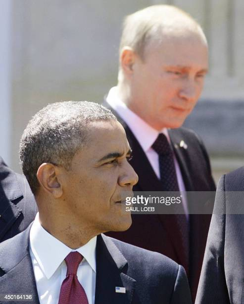 Russian President Vladimir Putin pasts US President Barack Obama as he arrives for a group photo of world leaders attending the DDay 70th Anniversary...