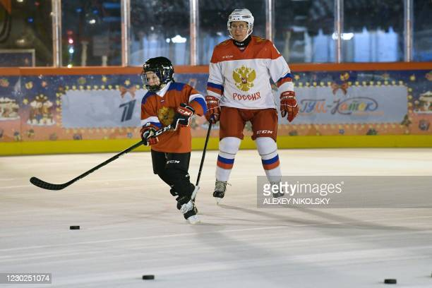 Russian President Vladimir Putin plays ice hockey with Dmitry Ashchepkov from Chelyabinsk at an outdoor ice skating rink in Red Square during the...