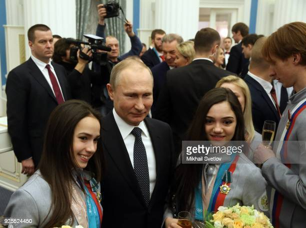 Russian President Vladimir Putin poses for a photo with figure skaters Olympic champions Alina Zagitova and Evgenia Medvedeva during his meeting with...