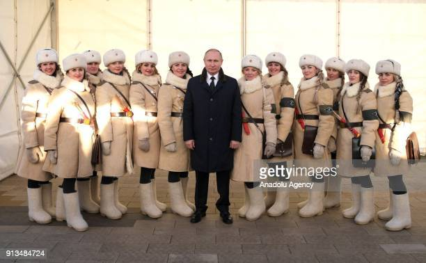 Russian President Vladimir Putin poses for a photo with girls dressed in Soviet WWII uniforms of traffic control officers as he attends the Names...