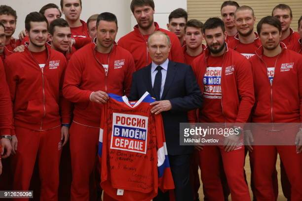 Russian President Vladimir Putin poses for a photo with national Olympic athletes who will take part in the upcoming 2018 Pyeongchang Winter Olympic...