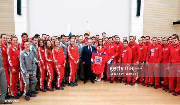 Russian President Vladimir Putin poses for a picture during a meeting with Russian athletes and team members who will take part in the upcoming 2018...