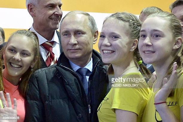 Russian President Vladimir Putin poses for a picture with girls as he visits a sports centre in the Ural's town of Nizhny Tagil on November 25 2015...