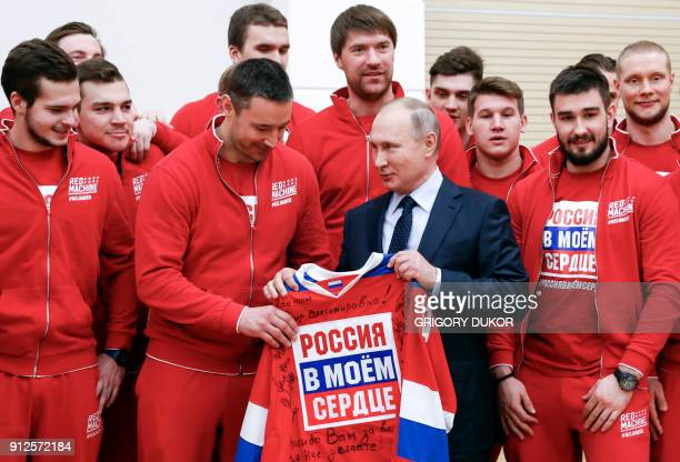 Russian President Vladimir Putin poses for a picture with ice hockey players during a meeting with Russian athletes and team members who will take...