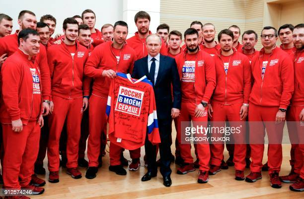 TOPSHOT Russian President Vladimir Putin poses for a picture with ice hockey players during a meeting with Russian athletes and team members who will...