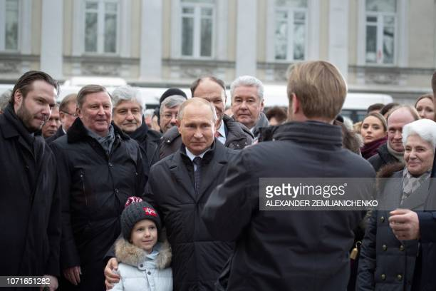 Russian President Vladimir Putin poses for pictures with Alexander Solzhenitsyn's relatives and officials after the unveiling ceremony of a statue of...