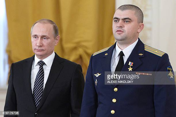 Russian President Vladimir Putin poses for pictures with Russia's Air Force Major Andrei Dyachenko after presenting him the Hero of Russia award...