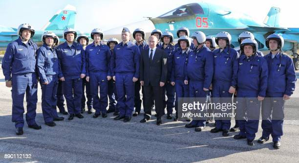 Russian President Vladimir Putin poses with Russian air force pilots during his visit to the Russian air base in Hmeimim in the northwestern Syrian...