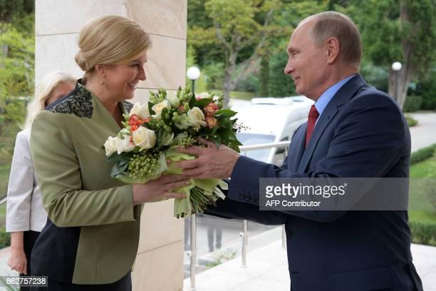 Russian President Vladimir Putin presents flowers to his Croatian counterpart Kolinda GrabarKitarovic during their meeting at the Bocharov Ruchei...