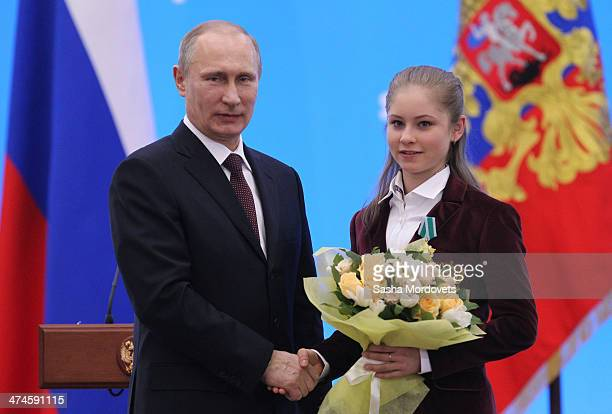 Russian President Vladimir Putin presents Olympic gold medalist in figure skating Yulia Lipnitskaya with an award during an awards ceremony for...