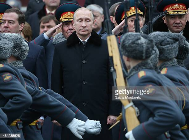 Russian President Vladimir Putin Prime Minister Dmitry Medvedev and Defence Minister Sergei Shoigu attend a wreath laying ceremony at the tomb of the...