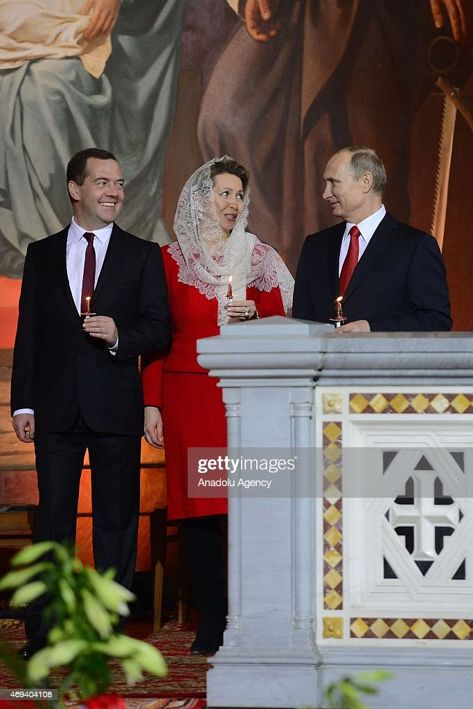 Russian President Vladimir Putin (R), Prime Minister Dmitry Medvedev (L) and his wife Svetlana (L2) attend the Easter service in Christ the Savior Cathedral in Moscow, Russia on April 12, 2015. Orthodox Christian believers mark the Holy Week of Easter in celebration of the crucifixion and resurrection of Jesus Christ.