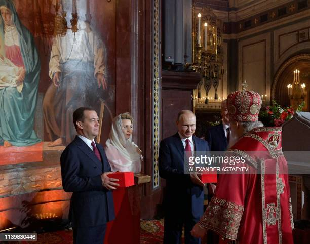 TOPSHOT Russian President Vladimir Putin Prime Minister Dmitry Medvedev his wife Svetlana and Moscow Mayor Sergei Sobyanin present gifts to Russia's...