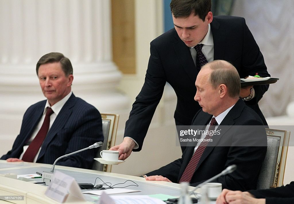 Russian President Vladimir Putin (R) receives a cup as Head of the Presidential Administration Sergey Ivanov (L) looks on during a meeting with G20 finance leaders in the Kremlin February 15, 2013 in Moscow, Russia. The G20 countries, that make up 90 percent of the worlds gross domestic product, is reportedly set to be dominated by the issue of counties using their currency fro economic gain over the weekend of meetings.