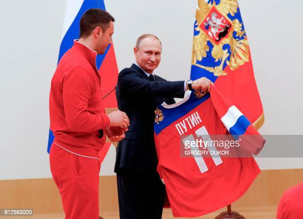 Russian President Vladimir Putin receives a jersey from ice hockey player Ilya Kovalchuk during a meeting with Russian athletes and team members who...
