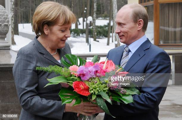 Russian President Vladimir Putin receives German Chancellor Angela Merkel with flowers during a short visit to Russia on March 08 2008 outside Moscow...