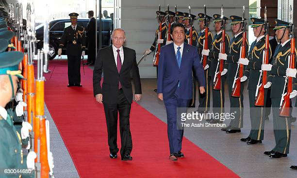 Russian President Vladimir Putin reviews the honour guard with Japanese Prime Minister Shinzo Abe at Abe's official residence on December 16 2016 in...