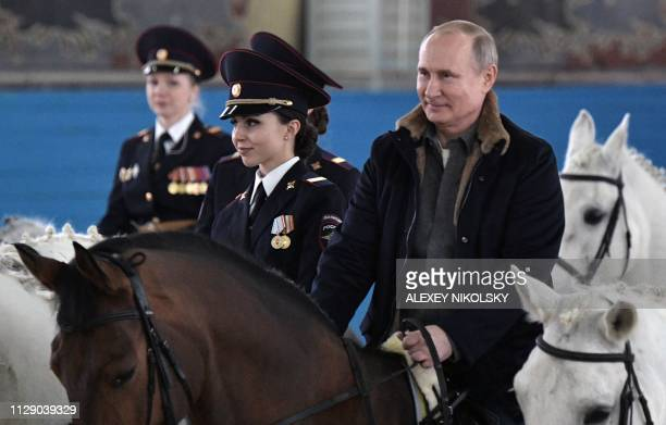 Russian President Vladimir Putin rides a horse along with female police officers as he visits a mounted police regiment ahead of International...