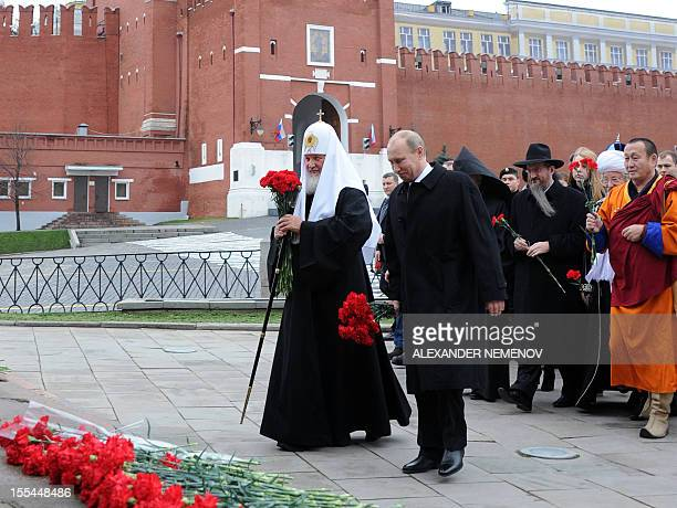 Russian President Vladimir Putin Russia's Patriarch Kirill and religious leaders hold flowers during a ceremony at the Red square in Moscow on...