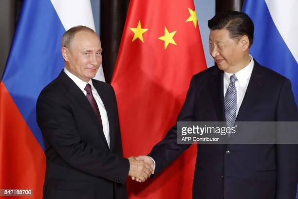 Russian President Vladimir Putin shake hands with Chinese President Xi Jinping during their meeting on the sidelines of the BRICS Summit in Xiamen on...