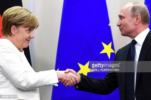 Russian President Vladimir Putin shake hands with German Chancellor Angela Merkel after a press conference during their meeting in Sochi on May 18...