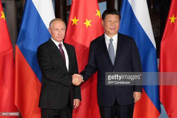 Russian President Vladimir Putin shakes hand with Chinese President Xi Jinping during their meeting on the sidelines of the BRICS Summit in Xiamen on...