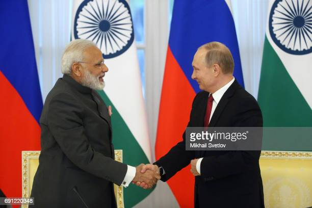 Russian President Vladimir Putin shakes hands and Indian Prime Minister Narendra Modi during their meeting at the Konstantin Palace on June 1, 2017...