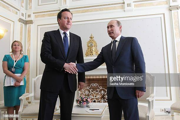 Russian President Vladimir Putin shakes hands as he receives Britain's Prime Minister David Cameron at his Bocharov Rruchey residence on May 10 2013...