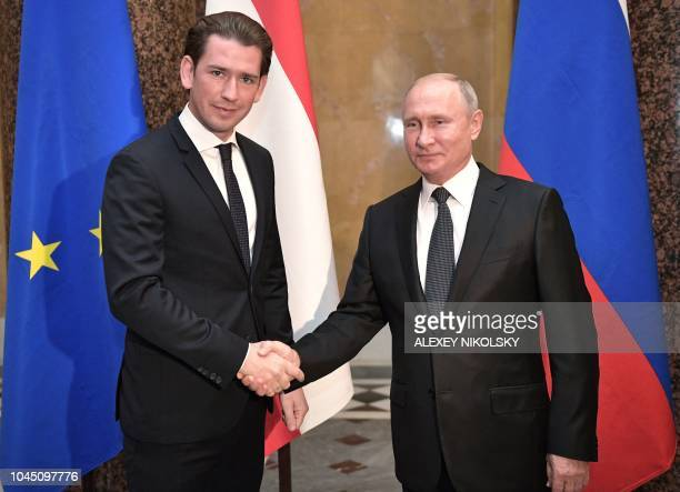 Russian President Vladimir Putin shakes hands with Austrian Chancellor Sebastian Kurz during a meeting at the State Hermitage Museum in Saint...