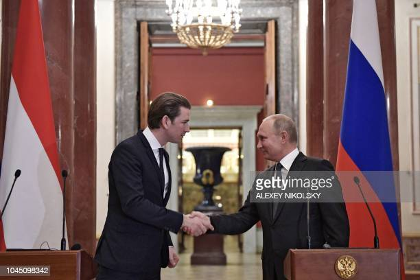 Russian President Vladimir Putin shakes hands with Austrian Chancellor Sebastian Kurz during a press conference following their meeting at the State...